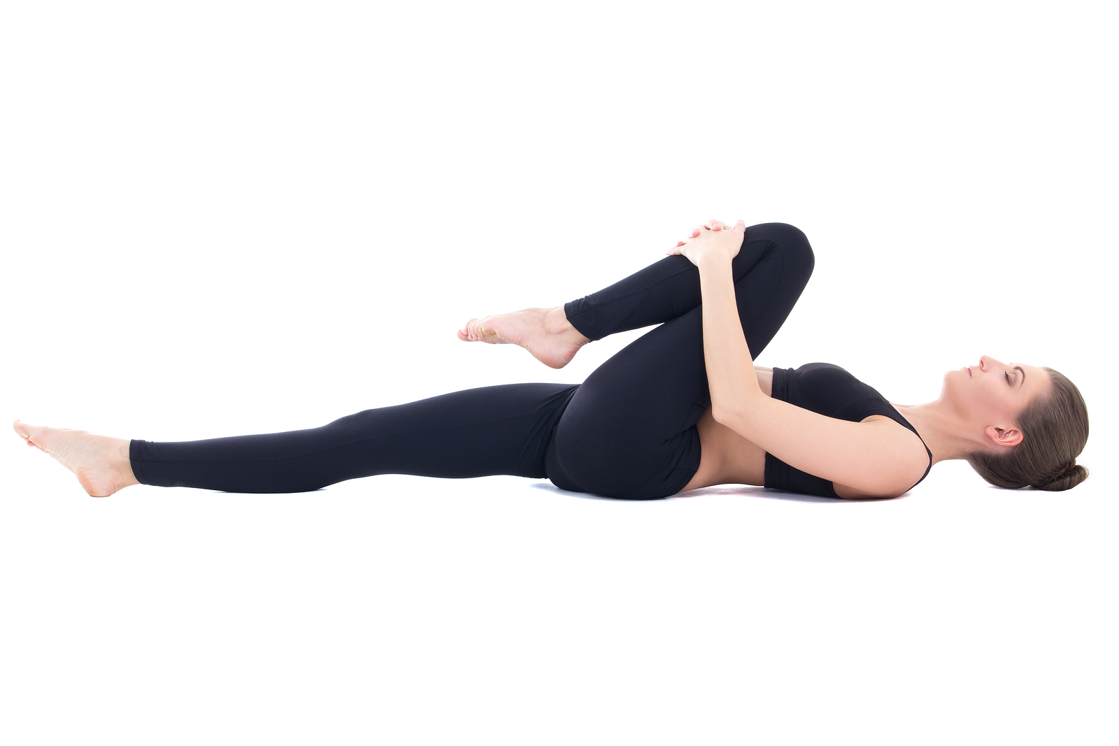beautiful sporty woman lying and doing stretching exercise isolated on white background